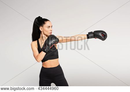 Brunette Young Sportswoman In Boxing Gloves Working Out Isolated On Grey