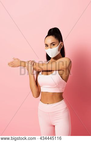 Young Sportswoman In Medical Mask Stretching Arm On Pink