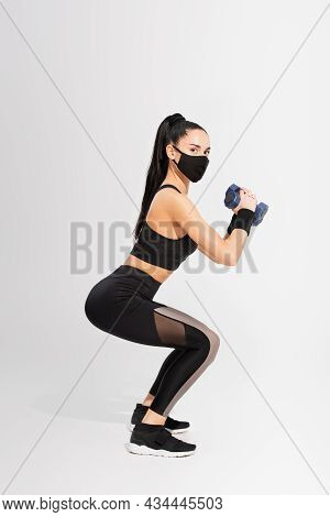 Full Length Of Sportswoman In Black Protective Mask Exercising With Dumbbells On Grey