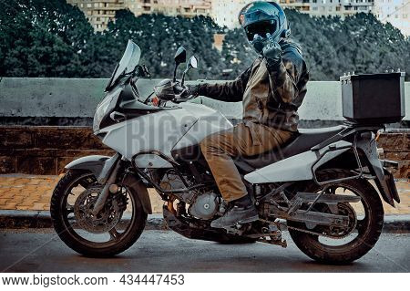 Motorcycle Rider In A Mirror Helmet On A Rusty Motorcycle In An Urban Environment. Biker Makes An Ob