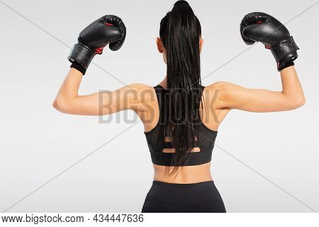 Back View Of Brunette Young Sportswoman In Boxing Gloves Isolated On Grey