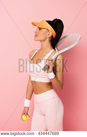 Pleased Sportswoman In Tennis Cap Holding Racket On Pink