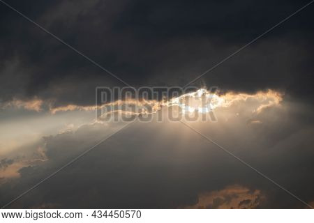 Cloudy Sky, Covered With Dark, Gloomy Clouds. Warm Evening Sun Rays Break From Behind The Clouds, Cr