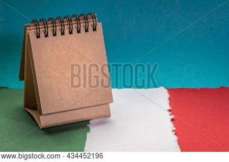 small, blank desktop calendar against paper abstract in colors of national flag of Italy (green, white and red), October is National Italian American Heritage Month