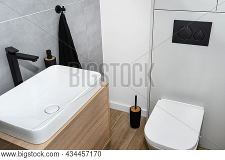 A White Ceramic Toilet With An Closed Flap In A Modern Restroom, A Floor Covered With Ceramic Tiles