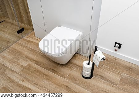 A White Ceramic Toilet With An Closed Flap In A Modern Bathroom, A Floor Covered With Ceramic Tiles