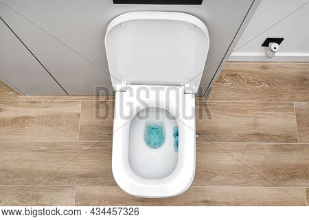 A White Ceramic Toilet With An Open Flap In A Modern Bathroom, A Floor Covered With Ceramic Tiles Im