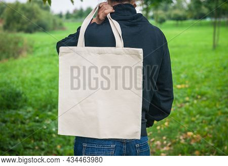 Stylish Man Holding White Blank Canvas Tote Shopping Bag Outdoor