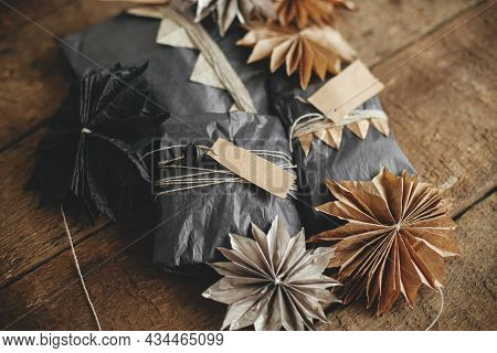 Stylish Christmas Gifts Wrapped In Craft And Black Paper With Tags And Swedish Paper Stars On Rustic