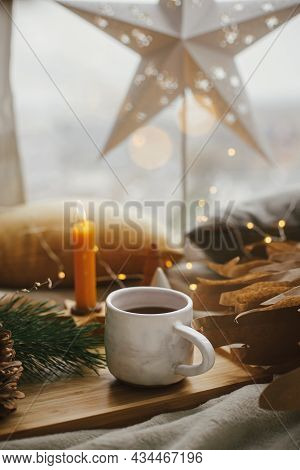 Warm Cup Of Tea On Background Of Illuminated Christmas Star, Christmas Lights, Pine Trees, Candle An