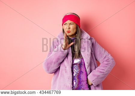 Fashion And Shopping Concept. Stylish Asian Middle-aged Woman In Fashionable Winter Clothes Smell So