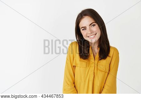 Image Of Cute And Romantic Woman Glancing At Camera, Smiling And Looking Shy, Standing Over White Ba
