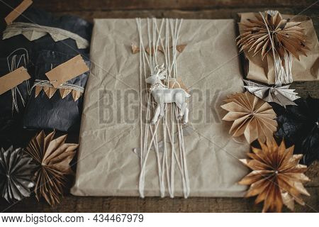 Stylish Christmas Gifts Wrapped In Craft And Black Paper With Reindeer Toy And Swedish Paper Stars O