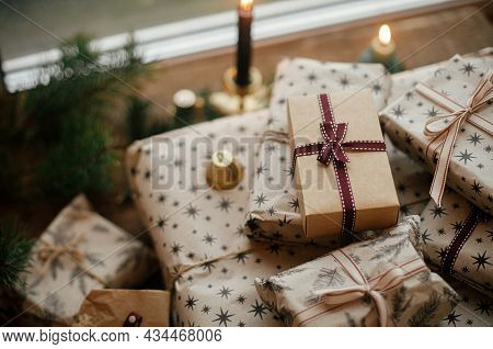 Stylish Christmas Gifts Wrapped In Craft Paper, Vintage Candles, Fir Branches And Bells On Rustic Wo