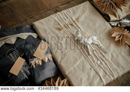 Stylish Christmas Gifts With Modern Decorations On Wooden Table. Xmas Present Wrapped In Craft And B