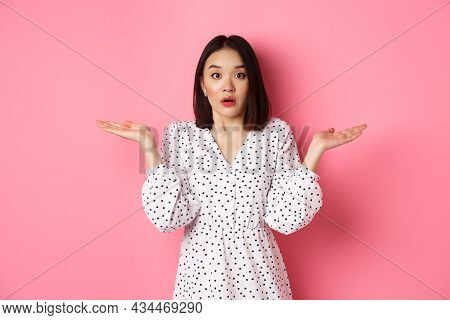Confused And Clueless Asian Girl Shrugging, Staring At Camera Puzzled, Dont Know What To Do, Spread