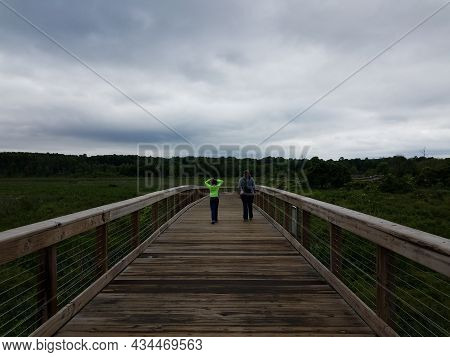 Mother And Child Walking On Boardwalk In Wetland