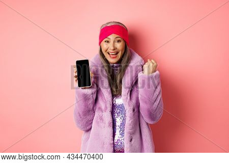 Online Shopping And Fashion Concept. Happy Asian Senior Woman Winning Prize In Internet, Showing Bla