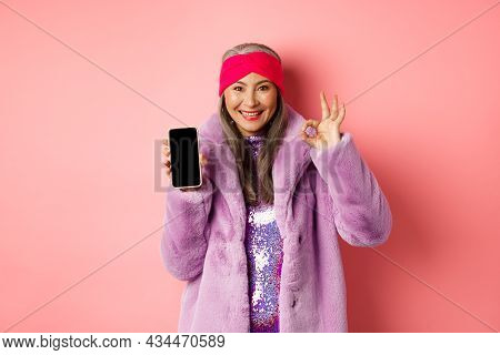 Online Shopping And Fashion Concept. Fashionable Senior Asian Woman Showing Blank Black Smartphone S