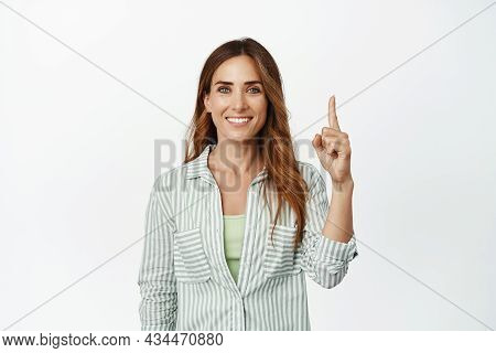 Image Of Confident, Ambitious Smiling Woman, Pointing Finger Up And Looking Determined, Showing Logo