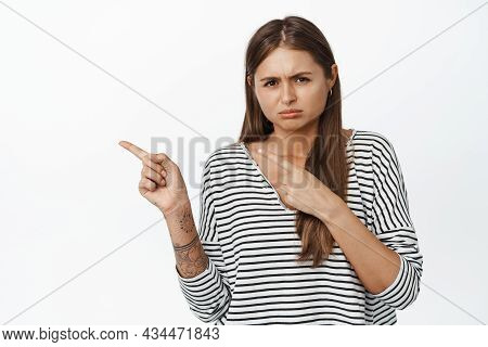Upset Sulking Girl Pointing Fingers Left And Sobbing, Looking Disappointed Or Sad, Standing Over Whi
