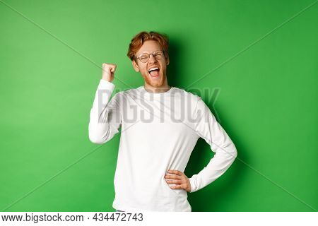 Young Cheerful Guy Scream Of Joy, Winning Prize And Celebrating, Making Fist Pump Gesture And Smilin
