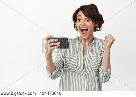 Image Of Happy Brunette Girl Watching Something On Mobile Phone, Cellular 4g Internet, Celebrating W