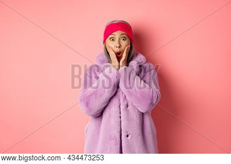 Fashion Concept. Trendy Old Asian Woman Looking Surprised At Camera. Mature Female In Purple Coat An