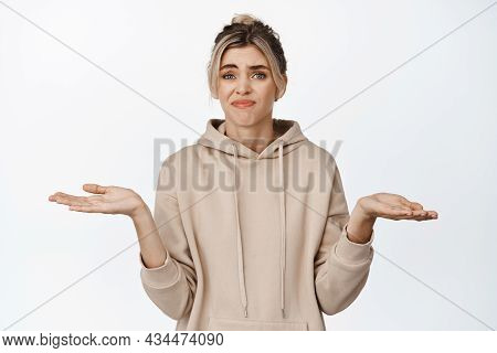 I Dont Know. Young Confused Woman Shrugging Shoulders, Holding Empty Hands Sideways, Nothing To Offe