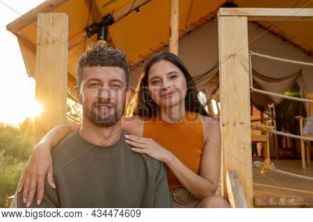 Happy young brunette woman embracing her husband while both enjoying summer rest by glamping house