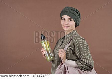 Horizontal medium studio portrait shot of stylish young adult Muslim woman holding bottle of fresh homemade lemonade smiling at camera, brown background