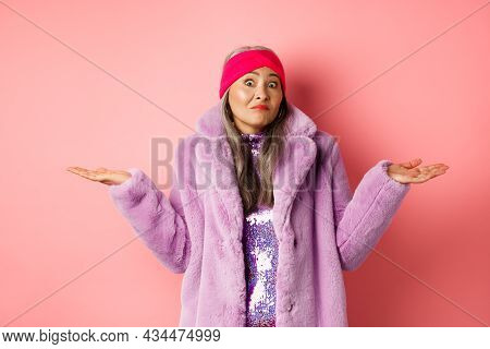 Fashionable And Funky Asian Old Woman Shrugging Shoulders, Looking Confused And Clueless, Standing I