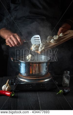 The Chef Cooks Meat Dumplings In A Saucepan In The Restaurant Kitchen. Close-up Of The Hands Of The