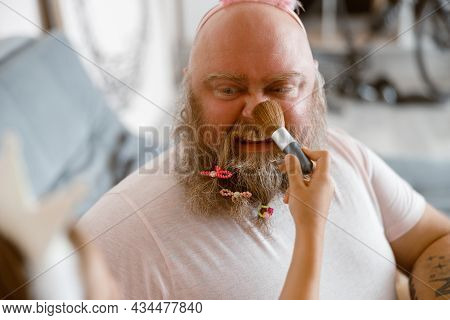 Plump Man Grimaces While Girl With Applies Makeup Onto His Nose In Contemporary Living Room