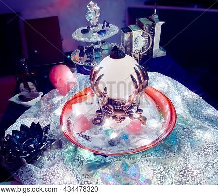Crystal Ball Divination Seance Table Set-up With Random Witchcraft Objects In Background