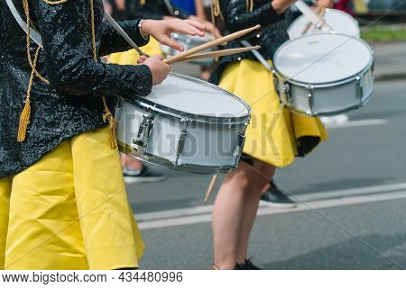 Close-up Of Hands Of Female Drummers In Yellow Black Vintage Uniform At Parade. Street Performance.