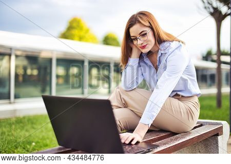 Young Redhead Caucasian Woman Reading On Laptop, Outdoors At City Park
