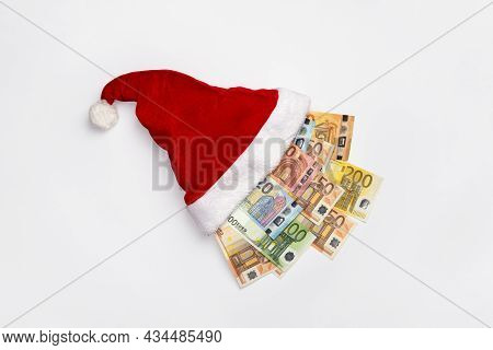 New Year Or Christmas Gift Concept. Money Inside Santa Hat. Christmas Hat Full Of Euro Bill Isolated