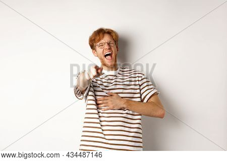 Young Man With Ginger Hair And Beard Pointing Finger At Camera And Laughing, Making Fun Of Someone H