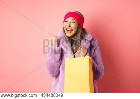 Shopping And Fashion Concept. Happy Asian Senior Woman Winning, Holding Paper Bag And Making Fist Pu