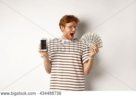 Amazed Redhead Man Showing Smartphone App On Blank Screen And Money, Winning Prize Cash Online, Stan