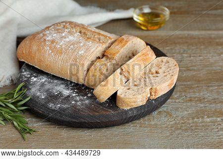Cut Delicious Ciabatta With Rosemary On Wooden Table