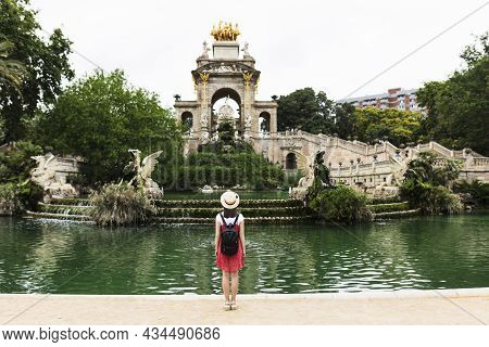 Back View Of Young Woman Traveler Visiting Ciutadella Park In Barcelona - Trendy Tourist With Backpa