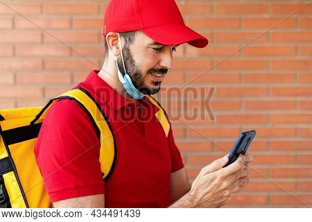 Cheerful Hispanic Delivery Man In Face Mask Using Mobile Phone In The Street While Delivering Packag