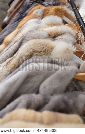 Rail of secondhand fur coats for sale in a thrift store or charity shop
