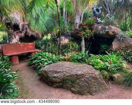 Stunning, Emerald Green Garden Hideaway Bench, Nestled Amongst Large Rock Boulders, And A Lush Fern