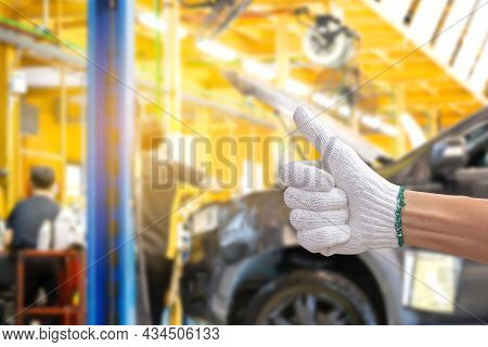 Technician Man Giving Thumb Up With Car Repair Service Centre Blurred Background