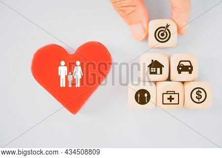 Hand Holding Wooden Cube With Dartboard Icon On Top Of Business Icon And Red Heart Shape With Family