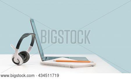 Laptop With Headphones On White Desk Banner