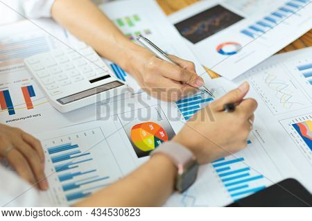 Businesspeople Working On Financial Reports, Graphs, Charts